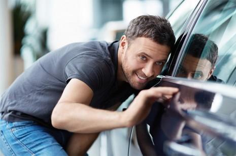 Мужчина и вымытый с воском автомобиль