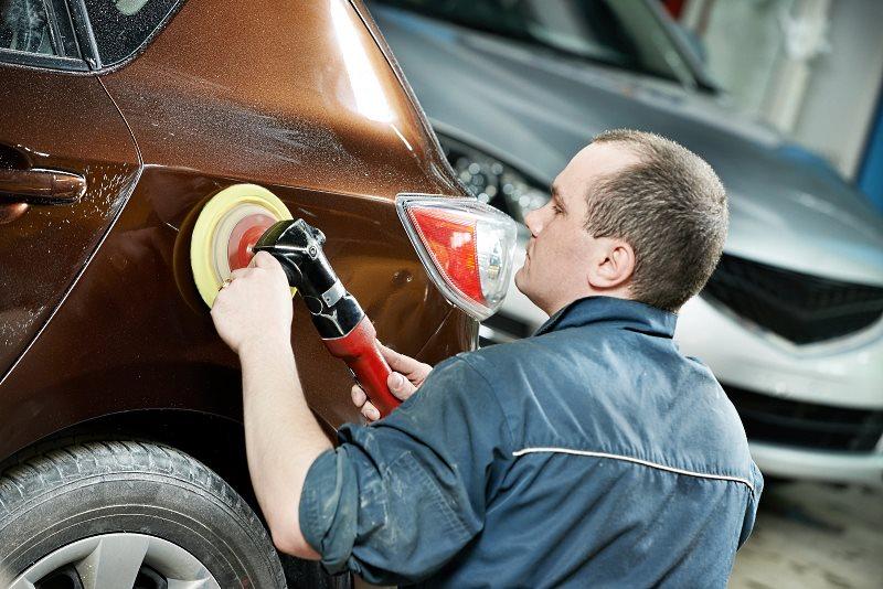 Мастер полирует автомобиль полировальной машинкой